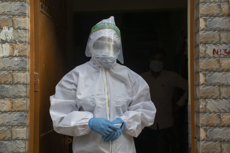 Portrait of woman wearing protective suit standing against wall