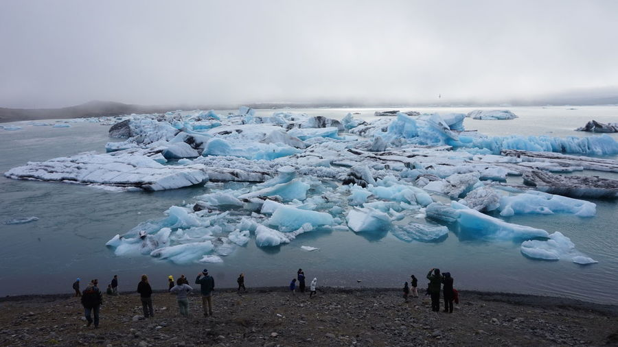 Tourists Standing At Beach By Glaciers Against Sky