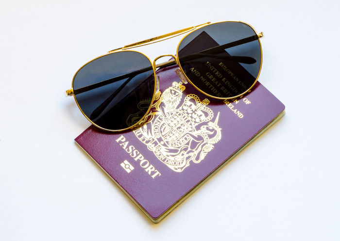 Travel Concept - Passport and Sunglasses British European  Holiday Immigration Official Passport Passports Travel United Kingdom Vacations Burgundy Citizenship Close-up Concept Document Glasses Identification Idyllic Legal Still Life Studio Shot Sunglasses Tourism White Background