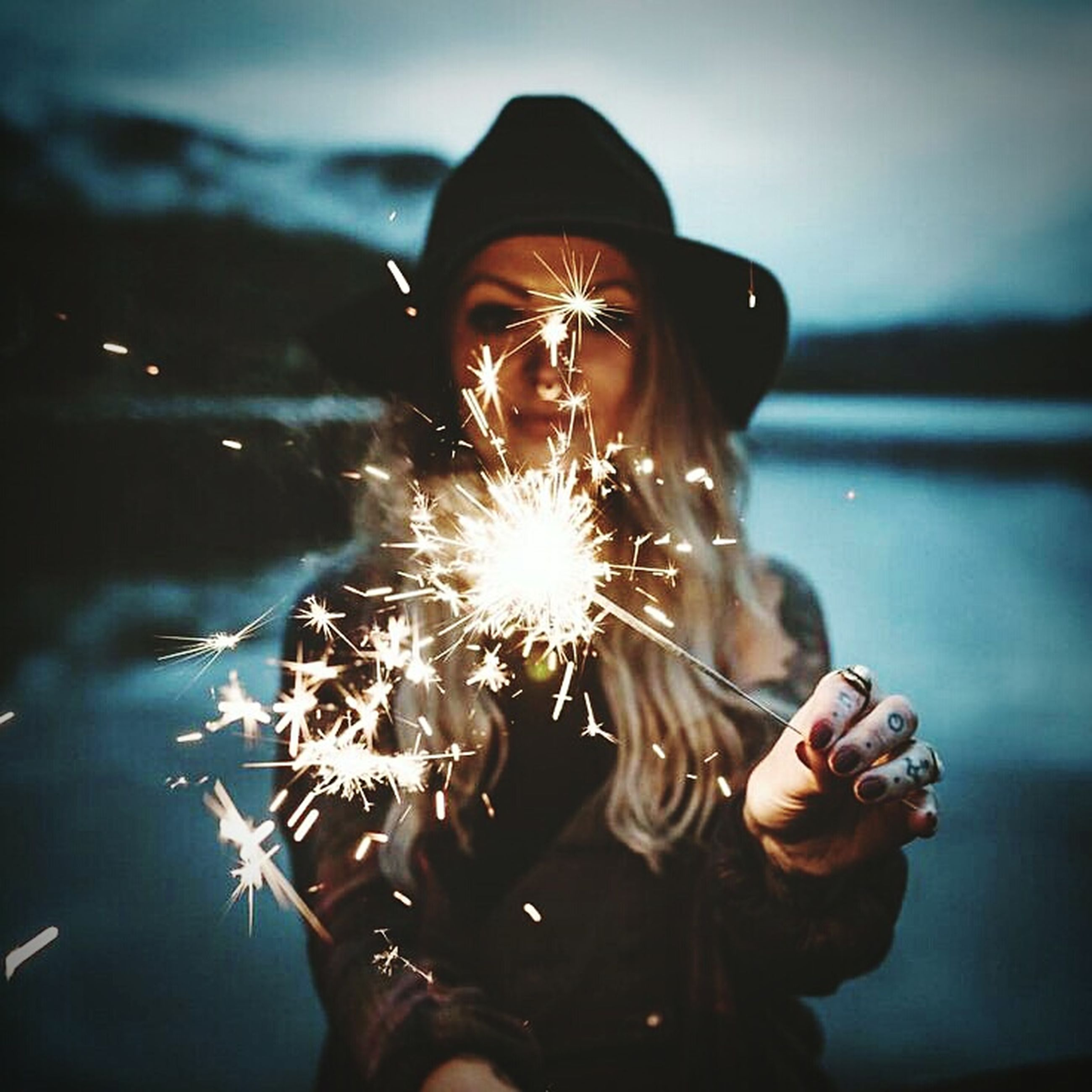 one person, holding, real people, sparkler, firework - man made object, lifestyles, motion, outdoors, women, illuminated, young women, young adult, close-up, human hand, sky, adult, day, people