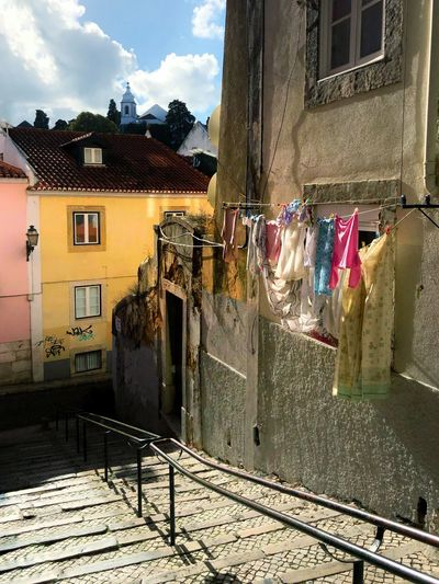 Clothes drying on street by buildings in city