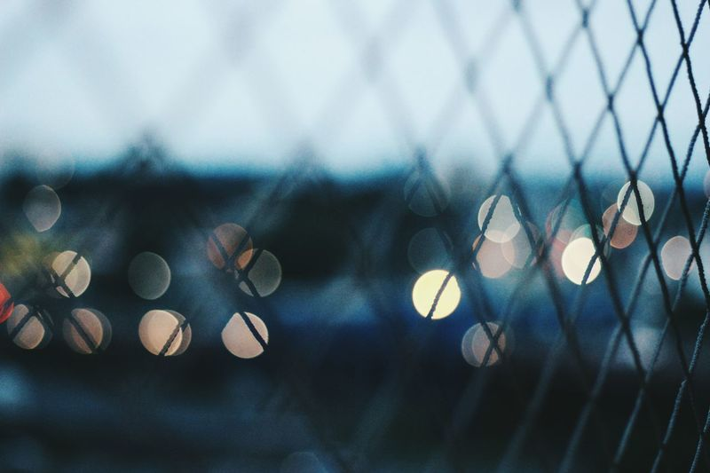 Defocused lights seen through chainlink fence at dusk