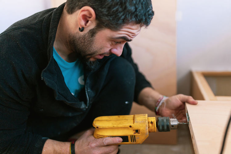 Man drilling wood in camper trailer