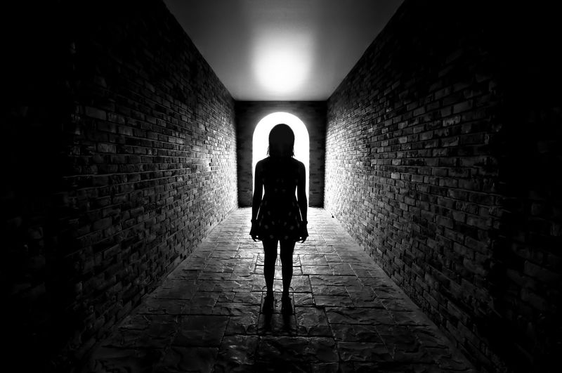 Silhouette of Lonely woman standing in the tunnel and Light at the end of the tunnel. Architecture One Person Rear View The Way Forward Built Structure Direction Full Length Walking Wall Real People Wall - Building Feature Lifestyles Illuminated Tunnel Brick Indoors  Brick Wall Building Arch Dark Alley Stone Wall Light At The End Of The Tunnel Underground Walkway