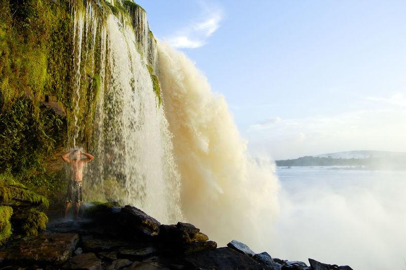 Man standing under waterfall against sky