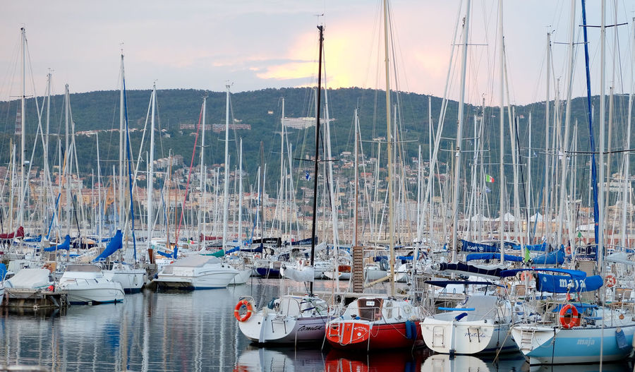 Boats moored at harbor by mountains against cloudy sky during sunset