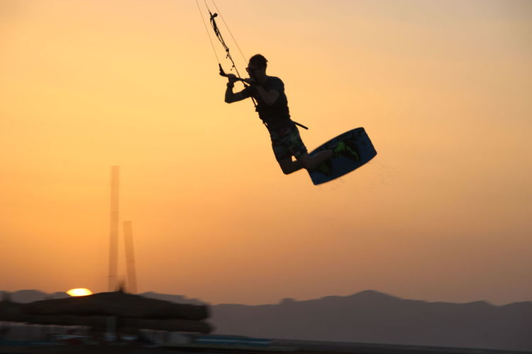 Low angle view of silhouette man swinging against sky during sunset