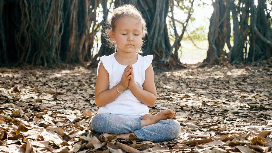 Full length of cute girl meditating while sitting on leaves
