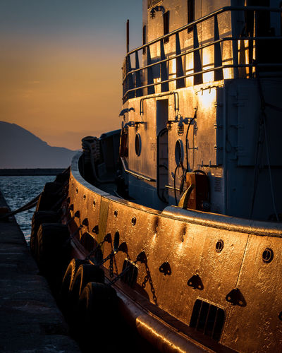 Abandoned ship moored on sea against sky during sunset