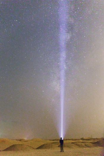 Rear view of man with flashlight on desert against star field at night