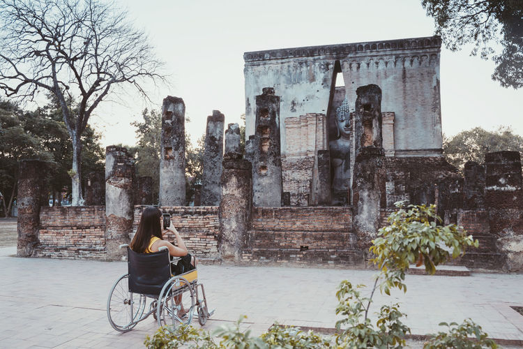 Rear view of woman photographing old ruins while sitting on wheelchair