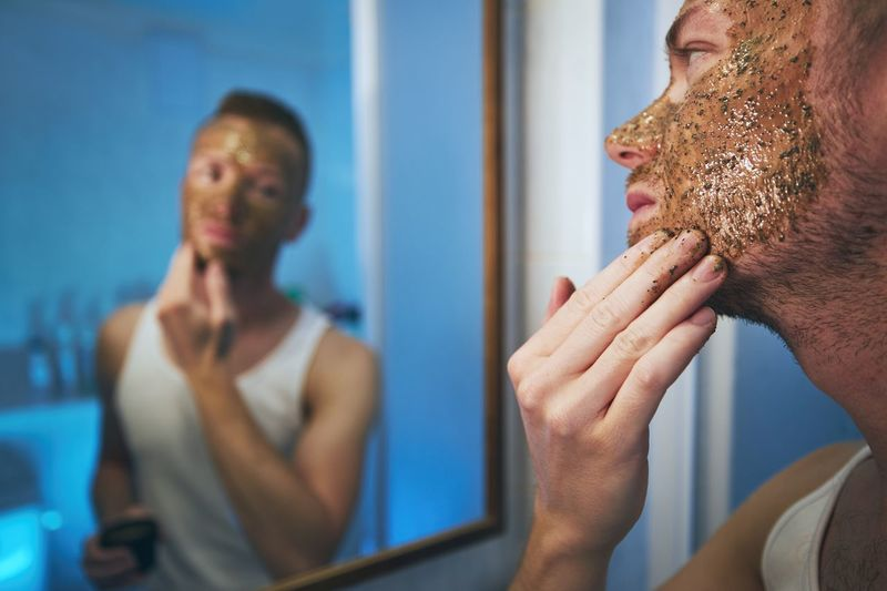 Close-up of man applying mask on face while looking in mirror at home