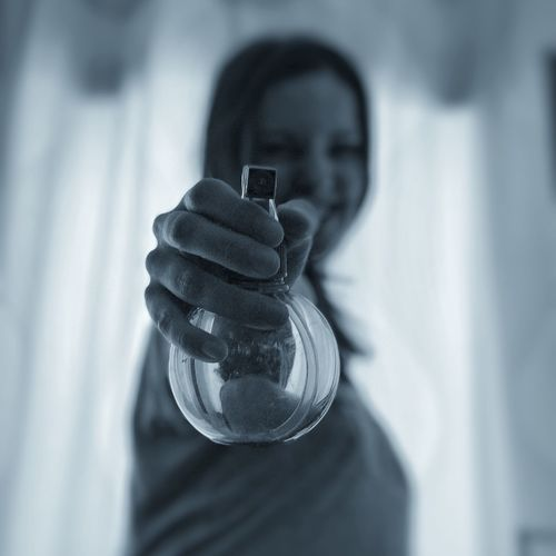 Close-up of woman holding glass sprayer at home