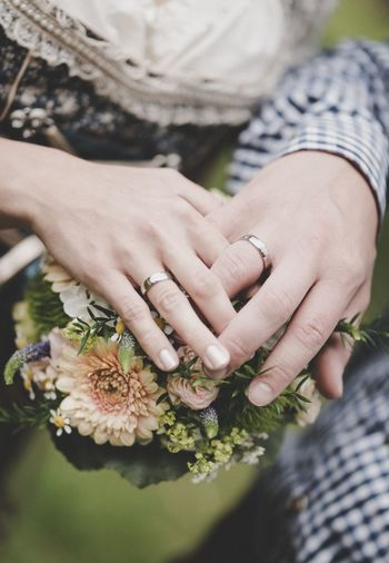 Midsection of couple with bouquet outdoors