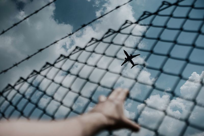 Cropped Hand Holding Fence Against Airplane Flying In Sky