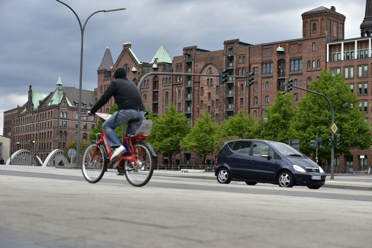 MAN RIDING BICYCLE ON ROAD BY BUILDINGS