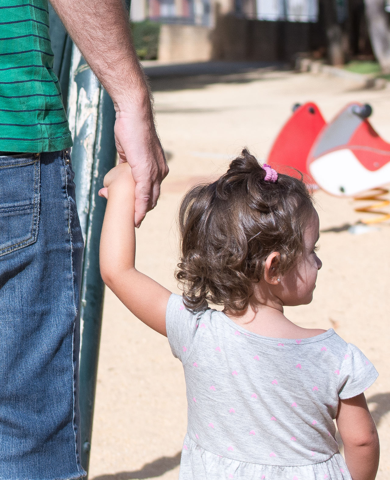 Midsection of father holding hand on daughter in park