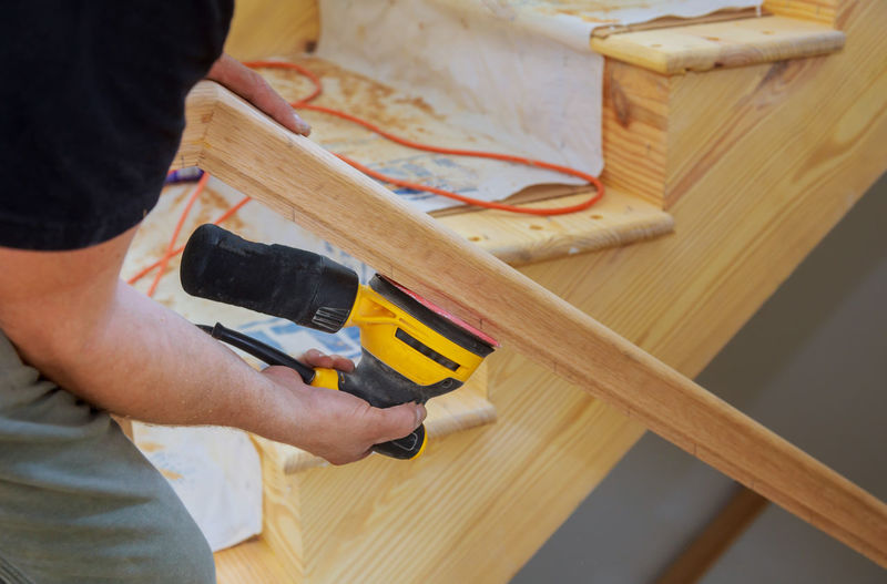 Midsection of carpenter working on wood at home