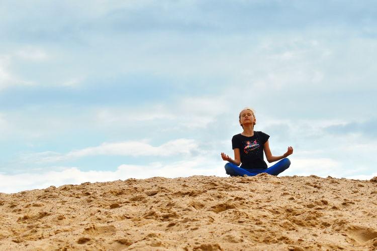 Girl doing meditation while sitting on sand at desert against sky