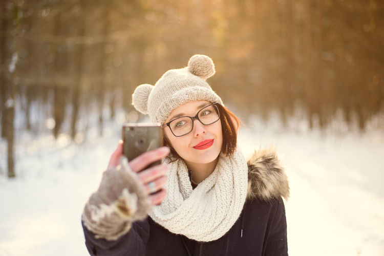 Beautiful Woman Beauty In Nature Cold Temperature Communication Day Glove Hat Holding Knit Hat Leisure Activity Lifestyles Mobile Phone Nature One Person Outdoors Real People Scarf Snow Standing Warm Clothing Winter Winter Coat Women Young Adult Young Women