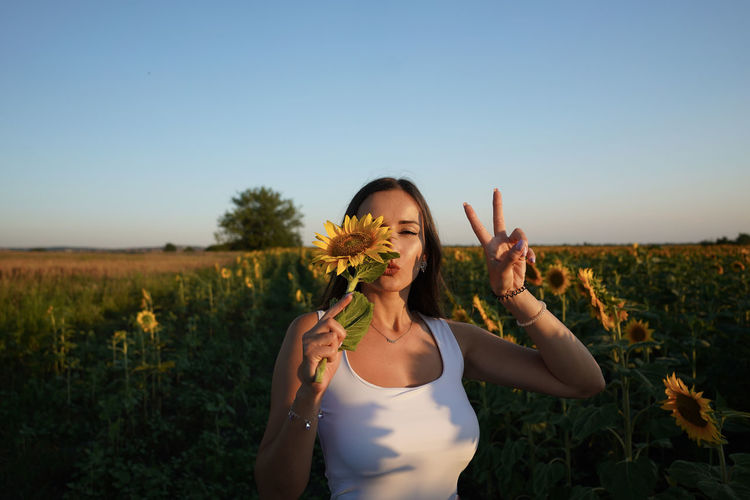 Portrait of young woman holding sunflower gesturing against sky during sunset