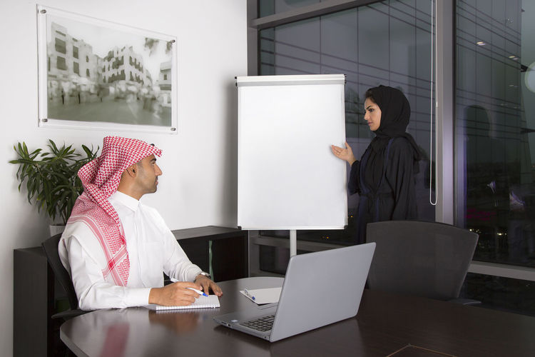Woman Standing By Whiteboard Looking At Man In Office