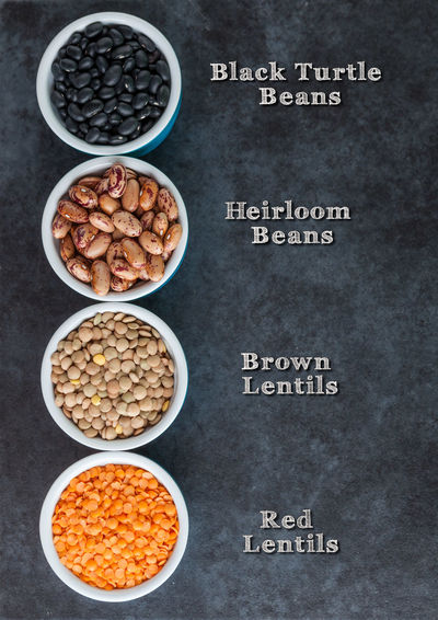 Red and brown lentils, heirloom beans, and black turtle beans on dark grungy surface. with labels. Top view vertical image with copy space. Beans Bowl Brown Lentils Close-up Day Food Food And Drink Freshness Healthy Eating Heirloom Beans Indoors  No People Nut - Food Red Lentils Text Top View Turtle Beans