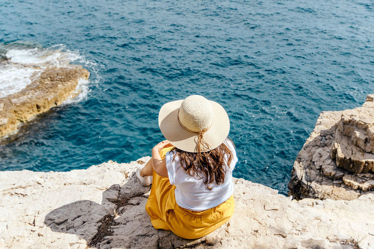Young woman in summer clothes and hat sitting on edge of cliff above sea.
