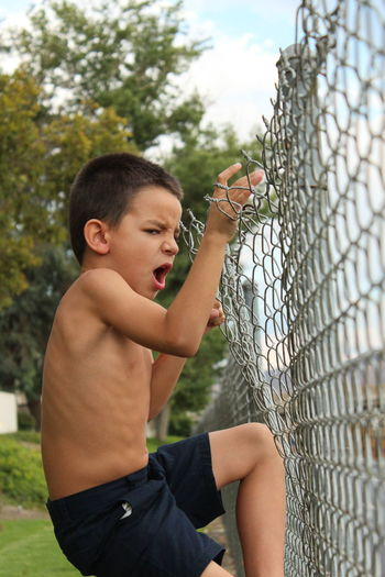 Baseball - Sport Baseball Helmet Boys Chainlink Fence Childhood Close-up Day Elementary Age Holding Human Hand Leisure Activity Lifestyles One Boy Only One Person Outdoors People Real People Shirtless