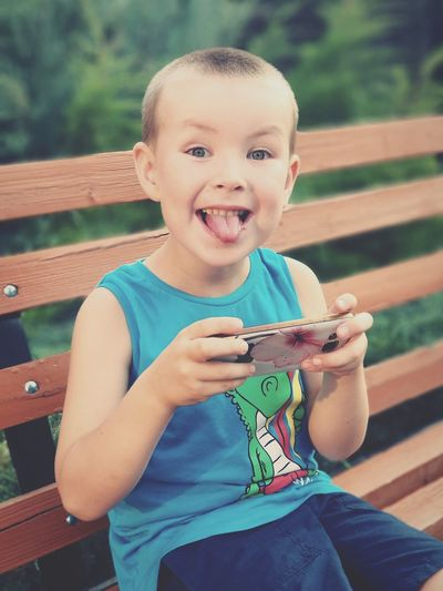 Portrait of boy with sticking out tongue holding mobile phone while sitting on bench