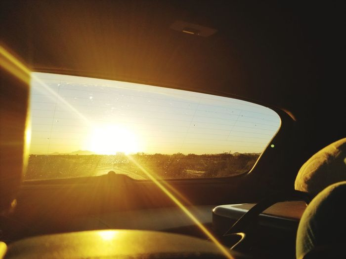 Travelling away from the day. Frame Sunrise Travel Luggage Cargo Land Vehicle Car Interior Sunlight Car Sun Windshield Vehicle Interior Sky Close-up