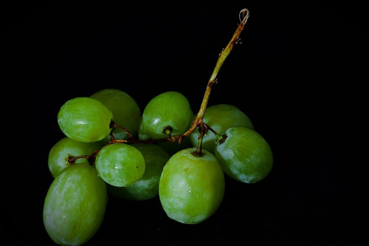 Close-up of grapes over black background