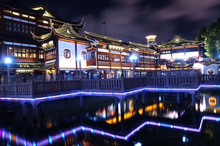 Illuminated city god temple over lake at night