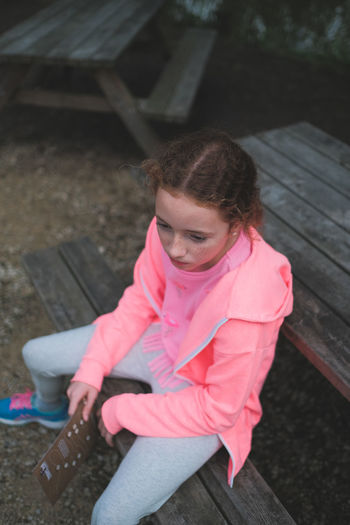 High angle view of girl sitting on bench