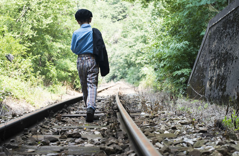 Railway Train Vintage Travel Alone Boy Child Suitcase Tunnel Interior Walking Rear View Railroad Track Rail Transportation Track One Person Full Length Transportation Plant Tree Day Men Nature The Way Forward Direction Casual Clothing Males  Mode Of Transportation Outdoors Rock Gravel