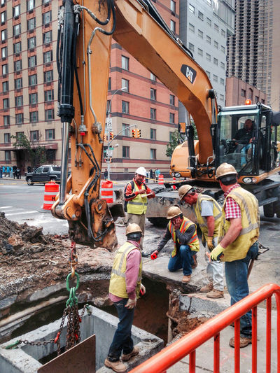 Construction workers discussing city sewer repair and water main utility placement. Workers Backhoe City Construction Digging Equipment Foreman HardHats Labor Laborer Landscape Maintenance Men Municipal Real People Repairs Sewer Street Utility Vest Water Water Main Working