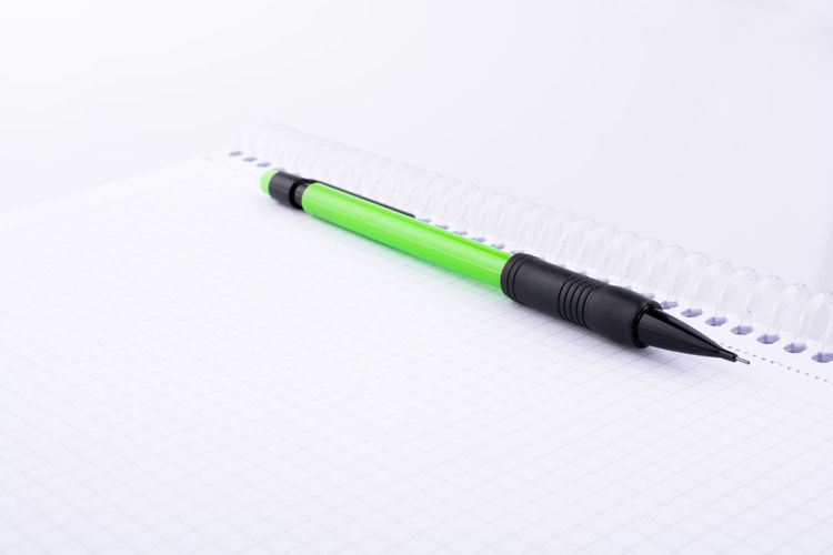 Close-up of pencil on spiral notebook