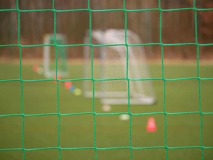 Soccer football net background over green grass and blurry stadium. close up detail of a soccer net