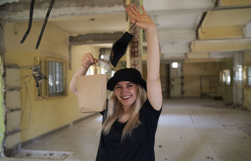 Portrait of smiling young woman standing against ceiling