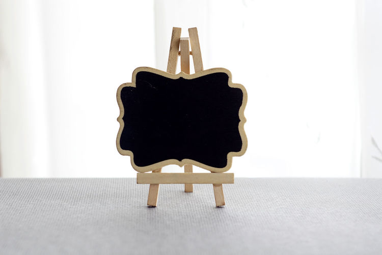a black board over white curtain background Absence Animal Representation Black Color Blank Close-up Copy Space Empty Flooring Indoors  Mammal No People Office Representation Seat Security Single Object Still Life Table Wall - Building Feature White Color Wood - Material