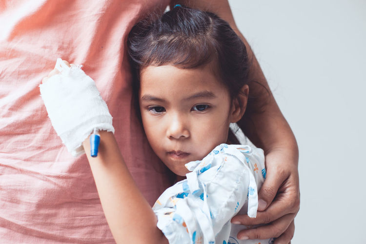Cute Girl With Injured Hand Embracing Mother