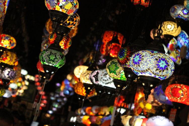 Close-up of illuminated lanterns hanging at market stall