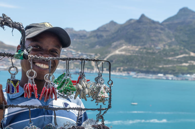 Portrait of smiling man in sea against mountains