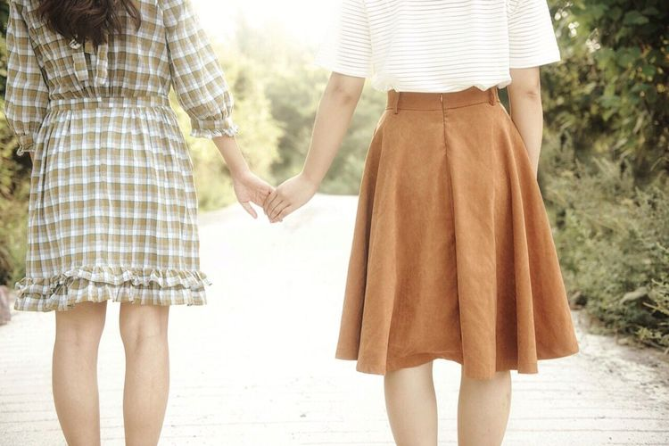 Midsection of women holding hands on road