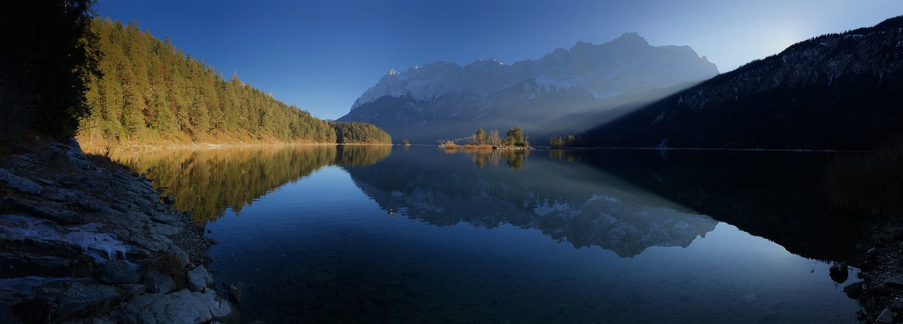 Scenic view of a sun-lit island in eibsee lake and reflection of zugspitze mountain against blue sky