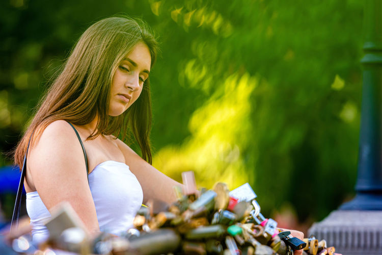 Portrait of woman standing by padlock outdoors