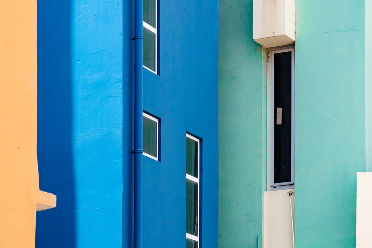 Green Green Wall Sunny White Frame Architecture Blue Blue Wall Brightly Building Building Exterior Built Structure Closed Day Door Full Frame Geometricity No People Outdoors Pattern Shadow Turquoise Colored White Window Yellow
