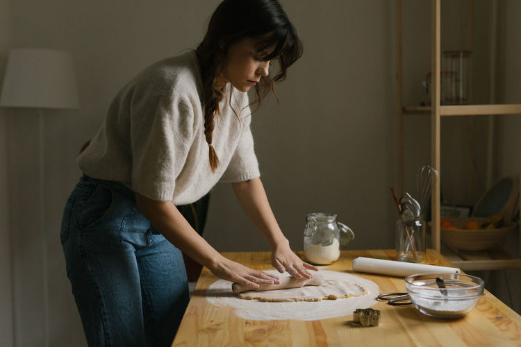 Midsection of woman standing on table at home