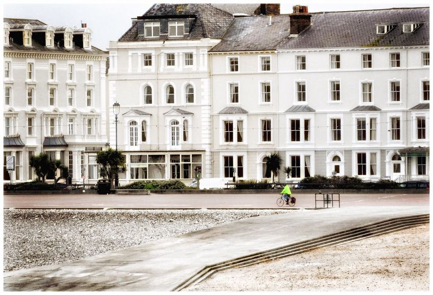 Lonely Cyclist in Llandudno Contrast of Bright Luminous Yellow against surrounding Pale Colours Eyemphotography Eye4photography  Eyeemphotography EyeEm Gallery EyeEmBestPics EyeEm EyeEm Best Shots Eye4photography  Cycling Single Person Buildings Shore EyeEm Best Edits Bright Colors Paint The Town Yellow