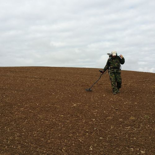 Low angle view of army soldier using metal detector on field against cloudy sky